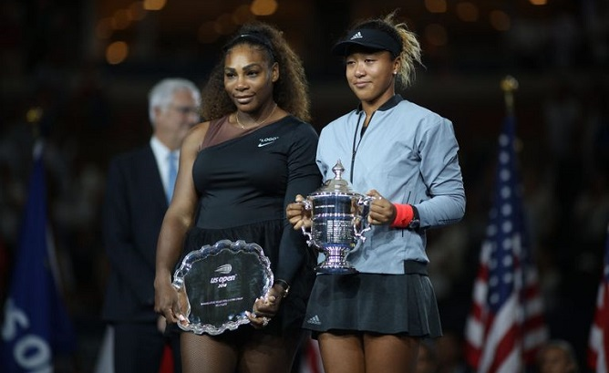 Naomi Osaka lifting US Open tropy with the runner up winner Serena Williams