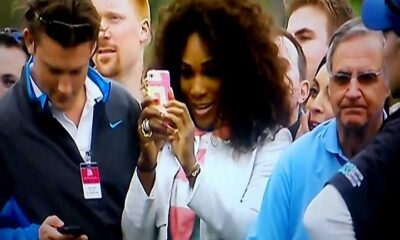 Serena Williams taking a picture of Tiger Woods